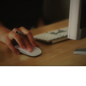 mano de mujer con ratón y portátil en escritorio